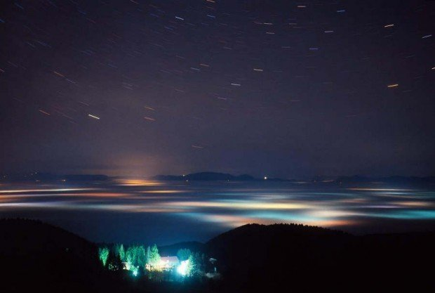 star trails above a sea of clouds