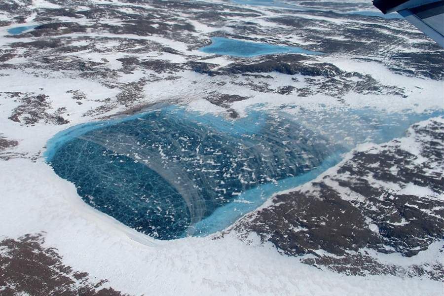 Meltwater pond nestled amid the rock-and-ice covered fringe of Greenland