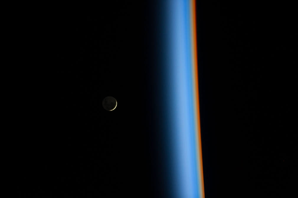 Crescent Moon rising above Earth's atmosphere