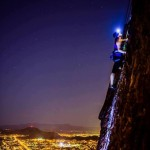 Woman climbing a vertical rock at night