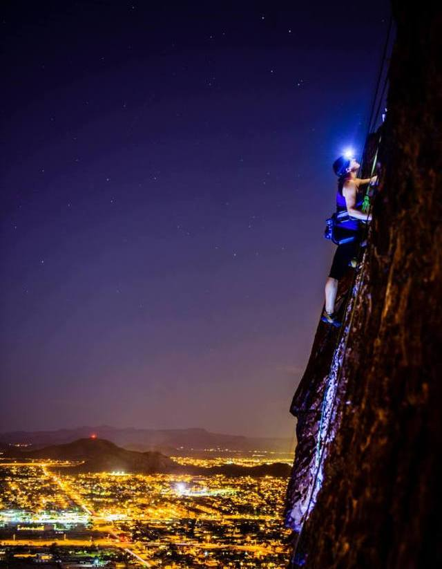 climbing a vertical rock at night