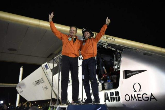 Andre Borschberg (L) and Bertrand Piccard after Solar Impulse 2 touches down in Abu Dhabi