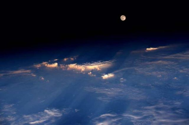 The full moon rises just before sunset, over western China