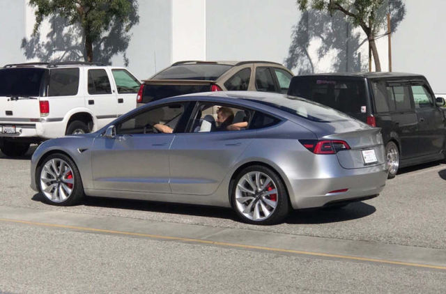 A Tesla Model 3 prototype driving down the streets