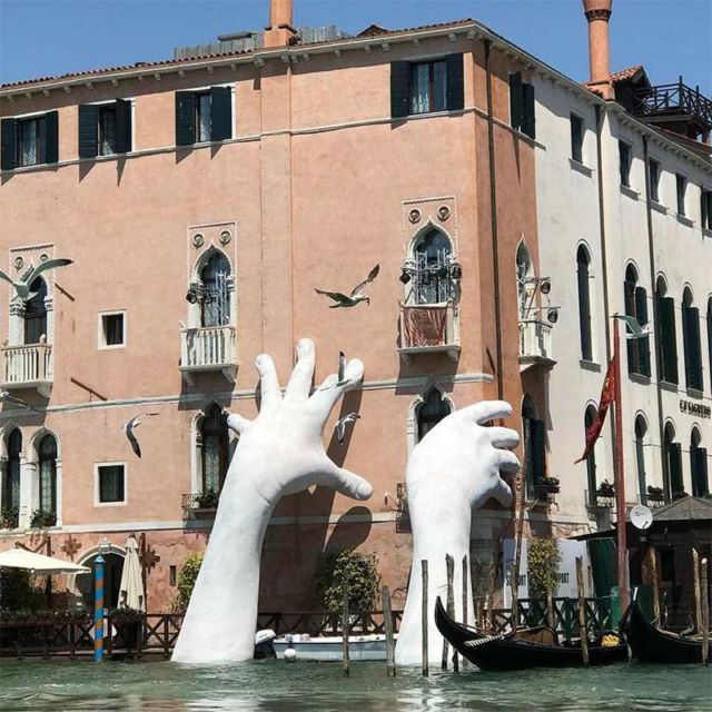 Giant Hands rise from a Canal In Venice