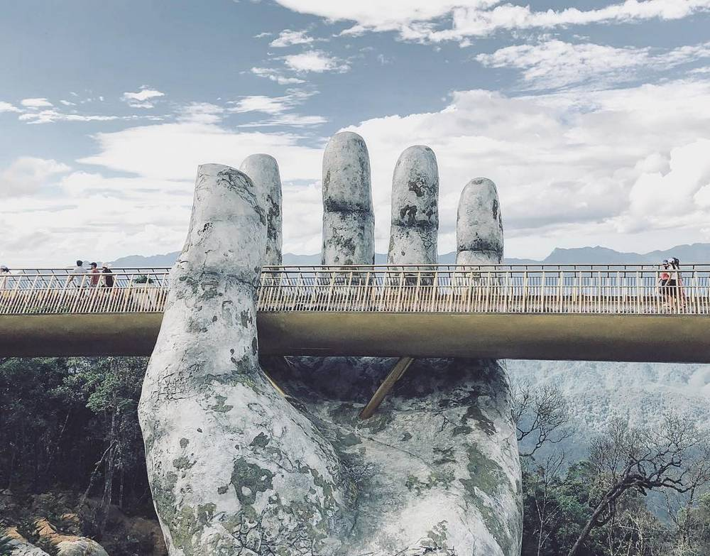 a giant pair of hands supporting a bridge in vietnam wordlesstech